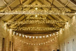 Guests enjoy wedding food inside Manor Mews wedding barn