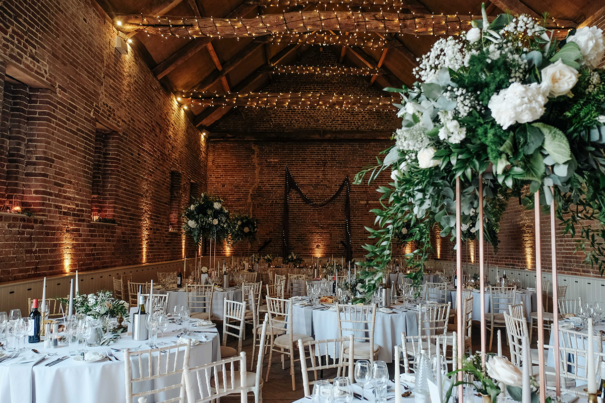 The barn was decorated with tall floral table centrepieces and twinkly fairy lights at this wedding in Norfolk